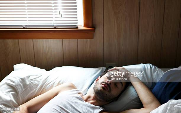 Cute Latin guy sleeping in bed near window