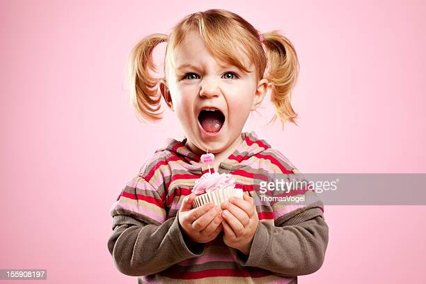 Cute litte girl dirty laughing and holding pink birthday cupcake