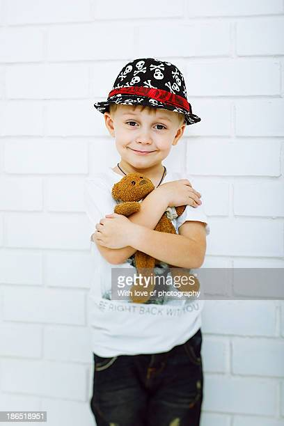 Cute little 5 years old boy in a hat with teddy