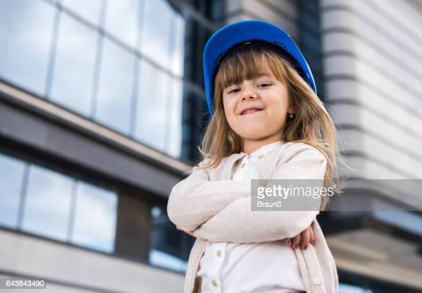 Cute little architect with her arms crossed outdoors.