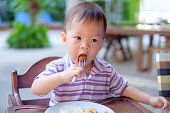 Cute little Asian 18 months / 1 year old toddler boy child sitting in high chair using fork eating whole cherry tomatoes, self feeding, common food choking hazards for babies & young children concept