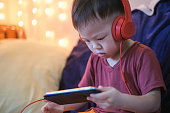 Cute little Asian 2 -3 years old toddler boy child listening to music with headphones from smartphone, Kids playing with phone in bedroom at home, Gadget-addicted children, internet addiction concept