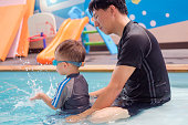 Cute little Asian 2 years old toddler boy child in swimming costume learn to swim at indoor salt water pool with father, Dad and son in Swimming school for small children, fun pool swim splash concept