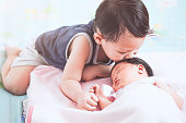 Cute little asian child boy kissing his newborn baby sister with love in vintage color tone