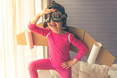 Cute little girl dressed like a pilot with toy wings is smiling and scanning the horizon while playing at home