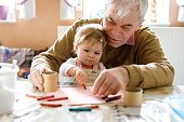 Cute little baby toddler girl and handsome senior grandfather painting with colorful pencils at home. Grandchild and man having fun together. Family and generation in love.