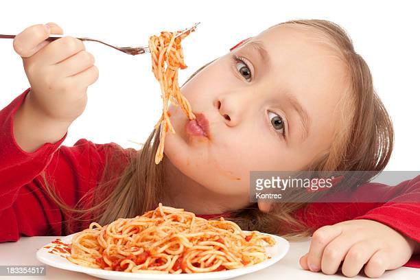 Cute little blond girl eating spaghetti