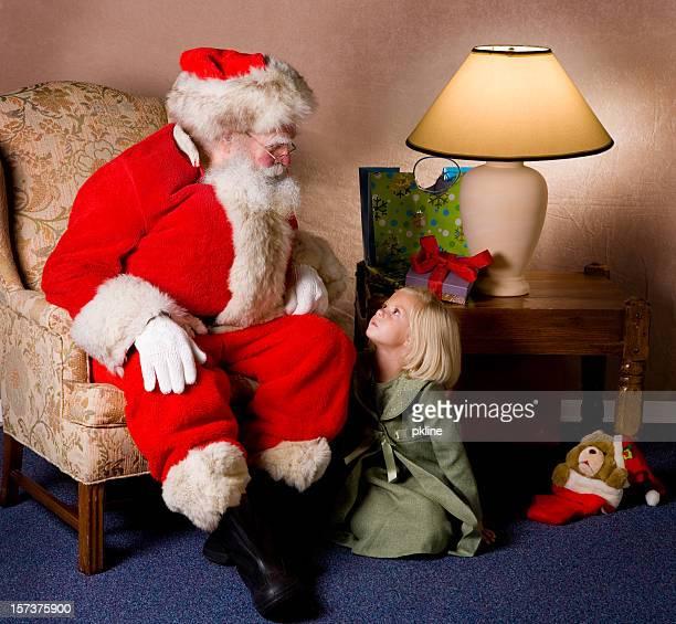 Carino piccolo ragazza bionda mette un look fino a Santa in poltrona