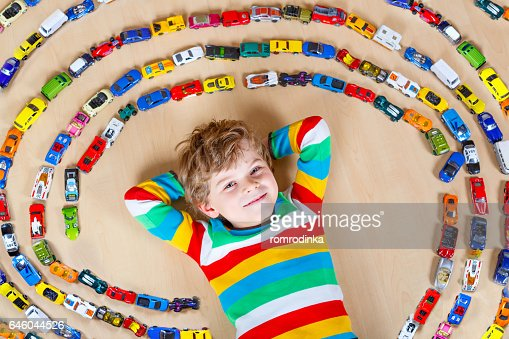 Cute little blond kid boy playing with lots toy cars : Stock Photo