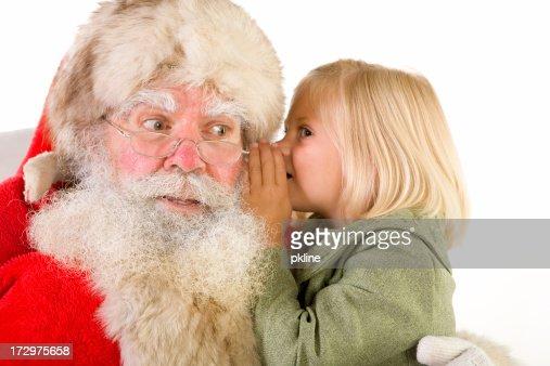 Cute little blonde girl whispers in Santa's ear
