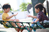 Cute little boy and girl playing rock-paper-scissors game in a playground