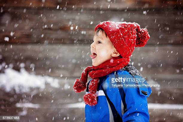 Cute little boy, catching snowflakes, wintertime