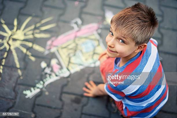 Cute little boy chalking on street