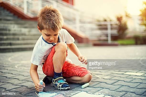 Cute little boy chalking on street