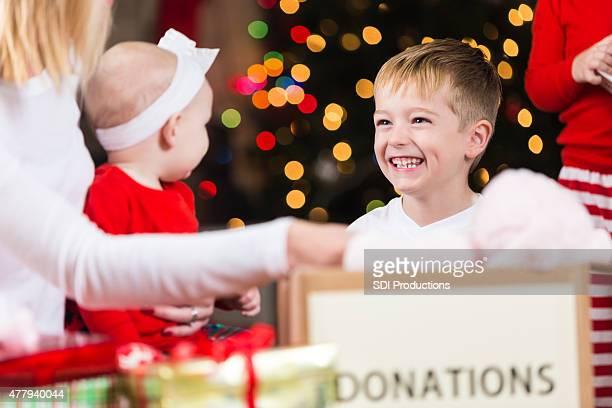 Carino piccolo ragazzo donazione all'ente di beneficenza giocattoli di Natale con tutta la famiglia