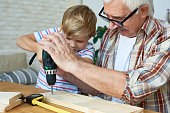 Portrait of senior man helping little boy make wooden model, teaching him carpentry and drilling boards