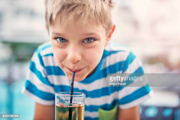 Cute little boy drinking apple juice at hotel restaurant