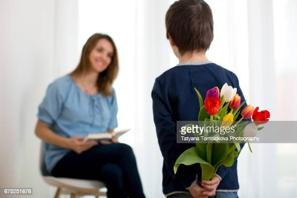 Cute little boy, giving tulip flowers bouquet to his mom for Mother's day, isolated image on white background, back light