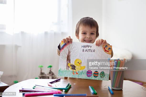 Cute little boy, holding picture with easter eggs