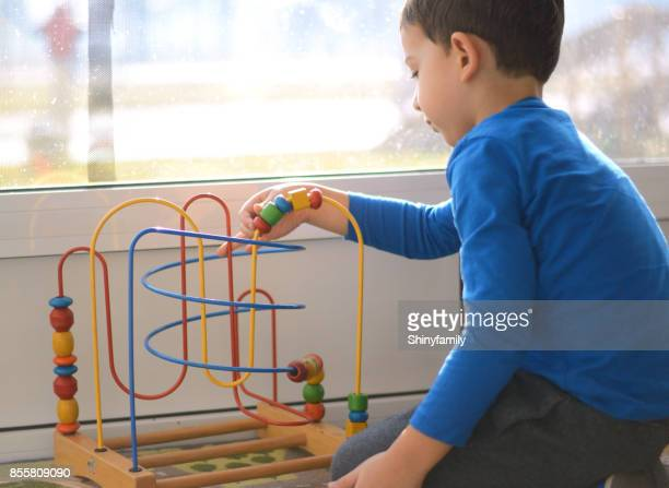 Cute little boy is playing with educational toys