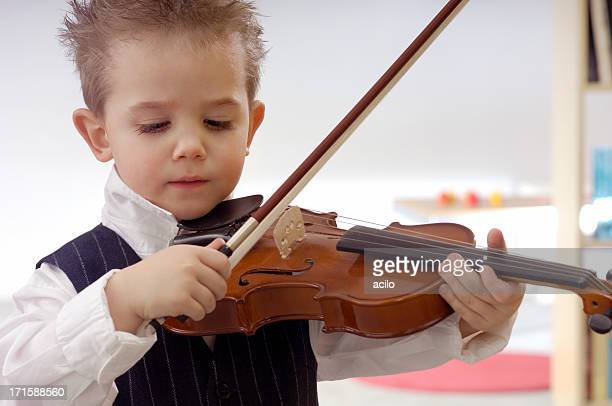 Cute little boy is practicing the violin