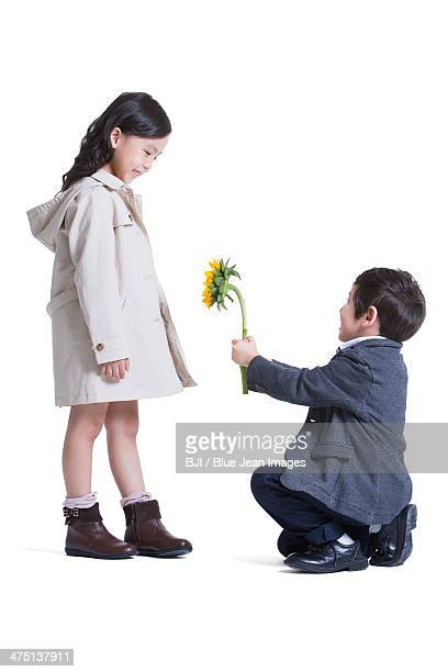 Cute little boy kneeling and proposing to girl