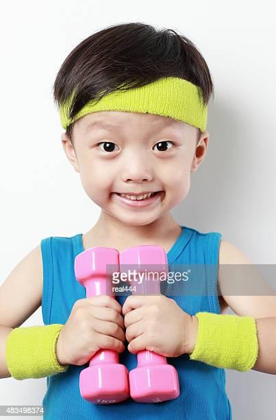 Mignon petit garçon en train de soulever des poids
