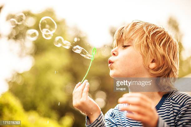 Cute little boy outdoors blowing bubbles