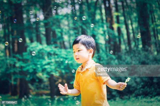 Cute little boy outdoors blowing bubbles