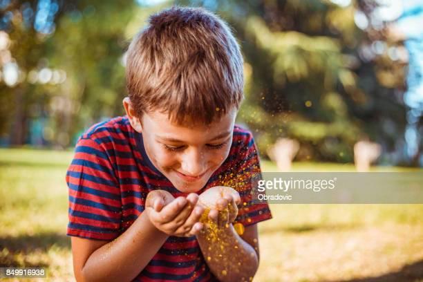 Niedliche kleine Junge draußen weht Glitzer-Staub