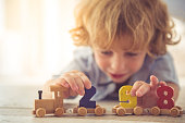 Cute little boy is playing with toy wooden train and numbers at home. Toy in focus