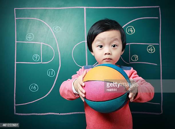 cute little boy playing basketball