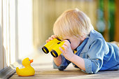 Cute little boy playing with rubber duck and plastic binoculars outdoors. Blonde hair child having fun with toy duckling