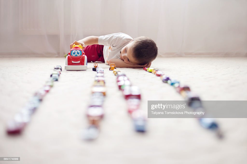 Cute little boy, playing with toy cars at home : Stock Photo