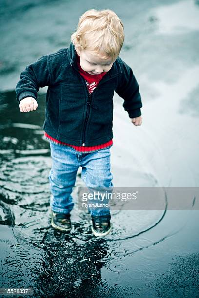 Cute Little Boy Plays in Puddle