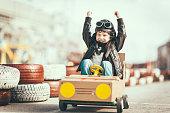 Cute little boy racing in a vintage go kart