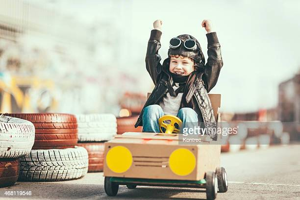 Cute little boy racing in a vintage go kart