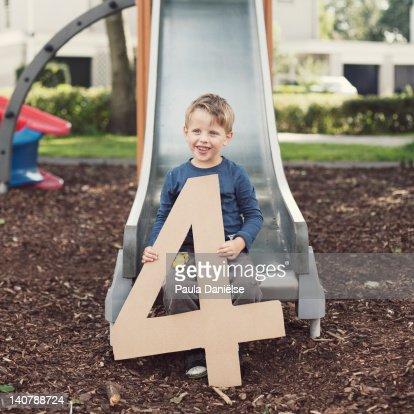 Cute little boy sitting on slide