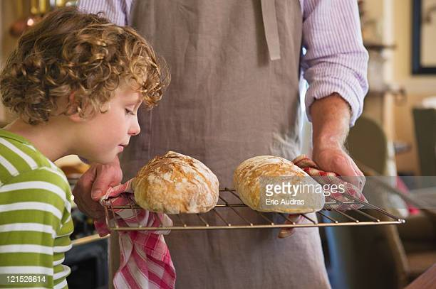 Cute little boy smelling baked bread in father's hand