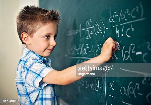 Cute little boy solving difficult mathematical problems