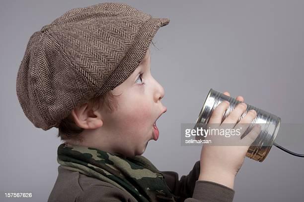 Süße kleine Junge überrascht Während der Kommunikation auf Dosentelefon