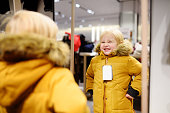 Cute little boy trying new coat during shopping. Fashion warm clothes for fall or winter. Kid/child in fitting room or in shopping center/mall