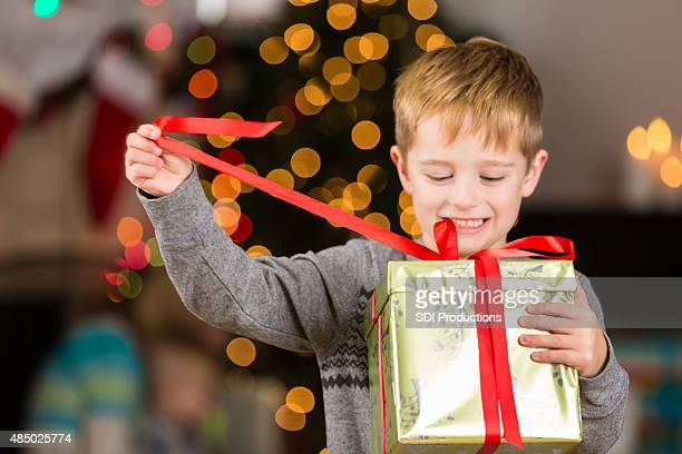 Cute little boy unwrapping Christmas present excitedly