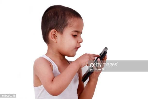 Cute little boy using touch screen smart phone