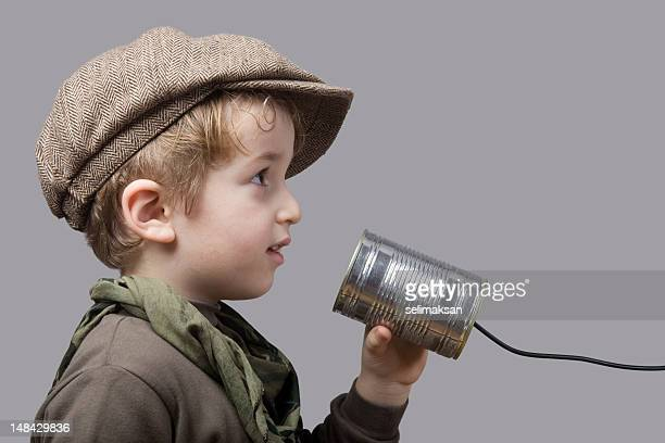 Cute Little Boy Wearing Hat Communicating On Tin Can Phone