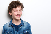 Close up portrait of a cute little boy with curly hair smiling on white background