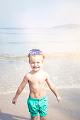 cute little boy with diving glasses at the beach