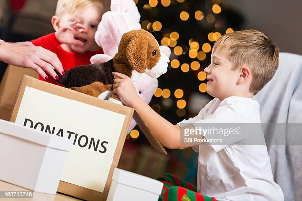 Süßen kleinen Jungen zu Spenden Sie Spielzeug für Weihnachten