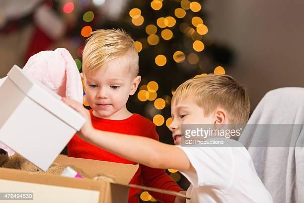 Süßen kleinen Jungen Spielzeug an Wohltätigkeitsorganisationen spenden während der Weihnachtszeit