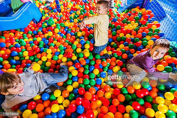 Cute little boys playing in the ball pool.